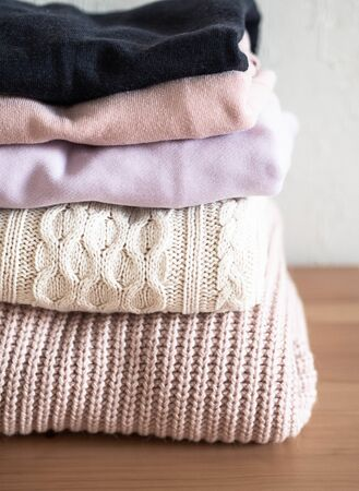Stack of warm knitted woolen sweaters pastel shades and dark blue on wood table
