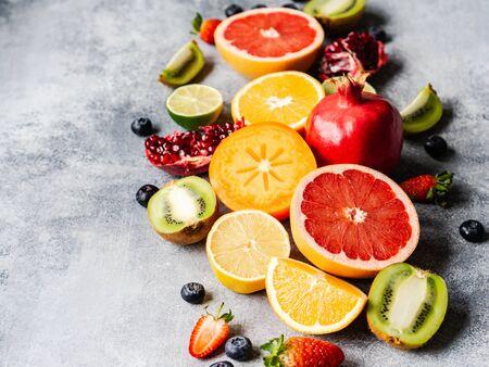 Composizione di frutta naturale sana stagionale multicolore con cachi, mirtilli, arancia, kiwi, fragole, pompelmo, melograno, fette d'arancia.