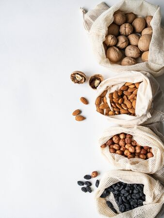 Reusable eco-friendly fabric bags for storage or shopping with various nuts and raisins on a white background.