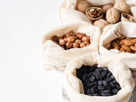 Reusable eco-friendly fabric bags for storage or shopping with various nuts and raisins on white background.