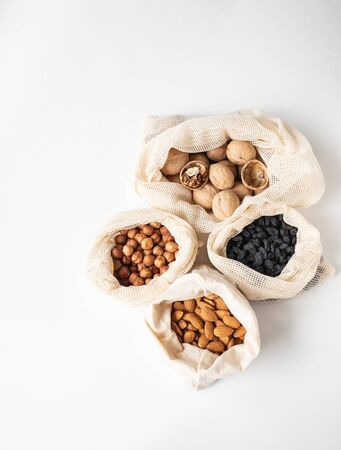 Reusable eco-friendly fabric bags for storage or shopping with various nuts and raisins on a white background. Top view Banco de Imagens