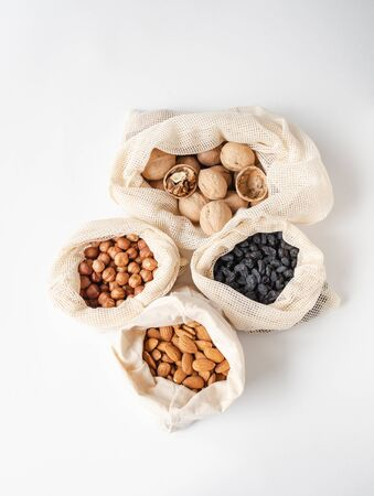 Reusable eco-friendly fabric bags for storage or shopping with various nuts and raisins on a white background. Top view Stockfoto