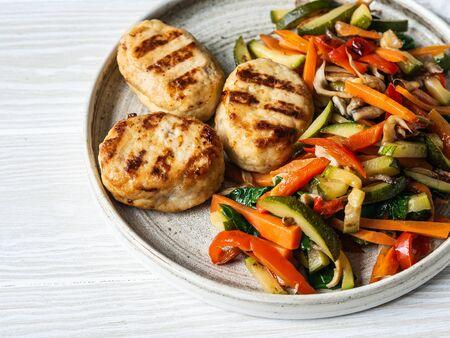 Putenschnitzel grillen, Gemüse steer braten auf einem Teller auf Holzbretttisch. Standard-Bild