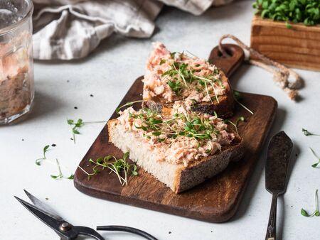 Zdrowe grzanki z pasztetem z łososia i świeżymi zielonymi kiełkami na chlebie bez drożdży na desce do krojenia Zdjęcie Seryjne