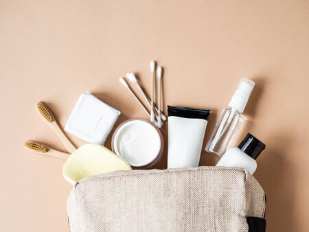 Travel cosmetic bag with the necessary means to care for women's skin. Cosmetics, dry shampoo, cotton buds, toothbrushes next cosmetic bag on a beige background. top view