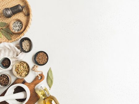 Flat lay of small bowls various dry spices, wood kitchen utensils and olive oil in glass bottle on a light background. Top view. copy space