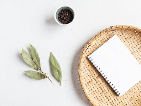 Kitchen notepad mock up for culinary text on wicker tray and spices on a light background. Minimalism kitchen concept. Top view. Copy space