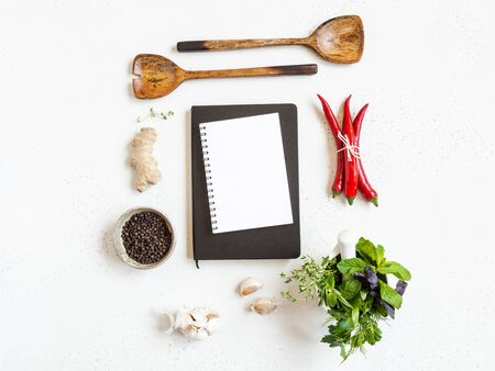 Kitchen background with open cookbook for recipes and various spices and herbs on light background. Top view. Copy space