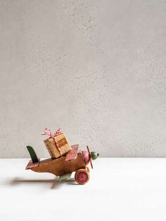 Christmas composition wooden vintage plane carrying Christmas gift for holiday. Copy space. Front view. holiday delivery concept Stock Photo