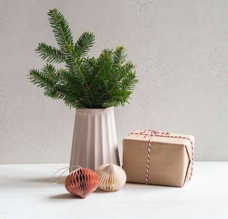 Fir branch in vase, origami christmas decor and Christmas gift. Eco-friendly Christmas concept. Front view. Copy space