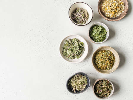 Various dry healthy herbs, plant flowers for brewing herbal tea in bowls on gray background. Top view. Copy space Фото со стока
