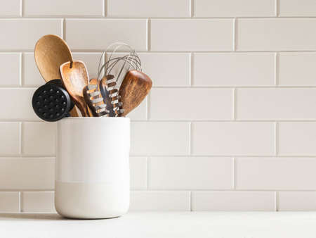 Stylish white kitchen background with kitchen utensils in ceramic jar on white countertop, copy space for text, front view Imagens