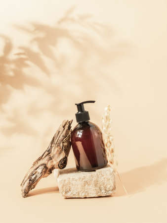 Stone podium and brown cosmetic bottle in creative composition on beige background with plant shadows. Copy space. Front view Stock fotó