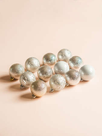 Creative composition of silver textured christmas balls of on a pastel peach background. Front view. Copy space Stock fotó