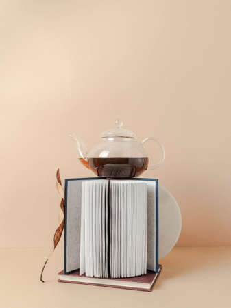 Creative trending composition with glass teapot with tea and books on pastel beige background. copy space. Front view Stock fotó