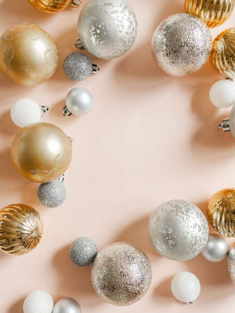 Frame of different colors and sizes christmas balls of on a pastel peach background. Top view. Copy space