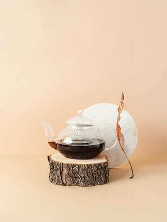 Creative trending composition with glass teapot with tea on natural wood podium and round marble board on pastel beige background. copy space. Front view