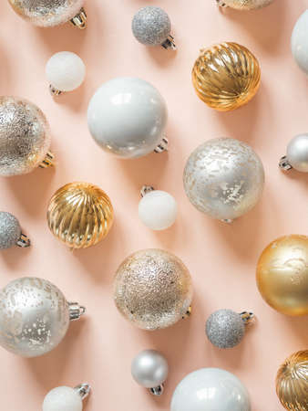 Flat lay of various christmas balls of on a pastel peach background. Top view.
