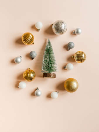 Frame of different colors and sizes christmas balls and christmas tree of on a pastel peach background. Top view. copy space
