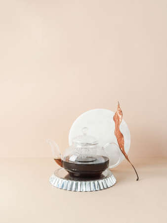 Creative trending composition with glass teapot with tea on metal podium and round marble board on pastel beige background. copy space. Front view Stock fotó - 158647793