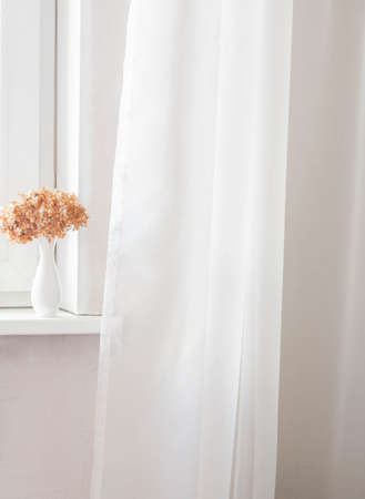 White vase with dried red hydrangea flowers on the windowsill and white tulle. Minimal. Copy space. Front view