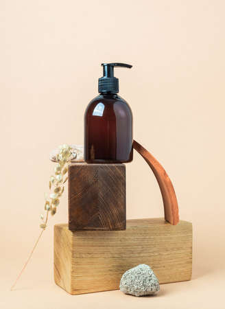 Wooden podiums and brown cosmetic bottle in creative composition with stones and fragments of terracotta on beige background. Copy space. Front view
