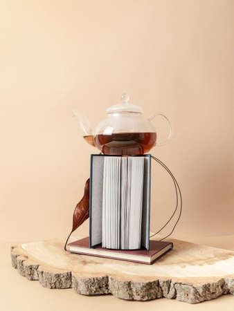 Creative trending composition with glass teapot with tea and books on wooden pedestal on pastel beige background. copy space. Front view