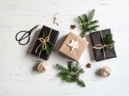 Flat lay of Christmas gifts sustainable packed. Christmas packaging in natural and black colors on a white wooden background. Top view. Copy space Stock fotó