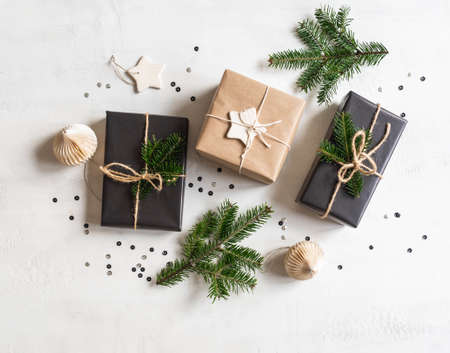 Flat lay of Christmas gifts sustainable packed. Christmas packaging in natural and black colors on a white texture background. Top view. Stock fotó