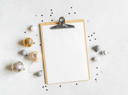 New year or christmas decor and and display a clipboard with a blank sheet of paper mock up on light background. Flat lay. Top view. Copy space