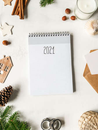 Frame of various Christmas decor and notebook with the inscription 2021 on white background. Top view. Copy space