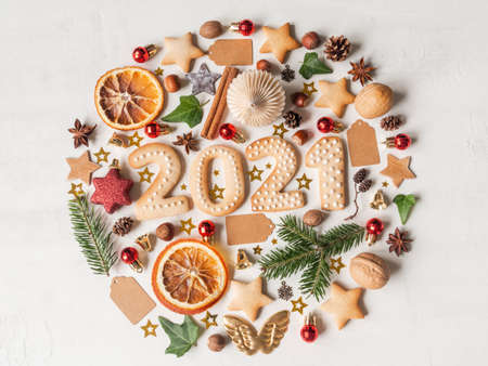 Round knolling composition of various items and food related to Christmas and gingerbread cookies in the form of numbers 2021on light background. Flat lay. Top view. Copy space Stock fotó