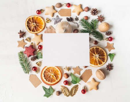 Round knolling composition of various items and food related to Christmas and blank postcard on white textured mackground. Top view. Copy space. Flat lay