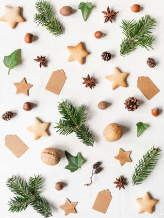 Natural christmas pattern from fir twigs and cones, cookies, nuts, wood stars, spices, and tags. Top view. Flat lay