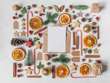 Multicolored Christmas knolling and open envelope with blank postcard for text on light textured background. Flat lay. Top view