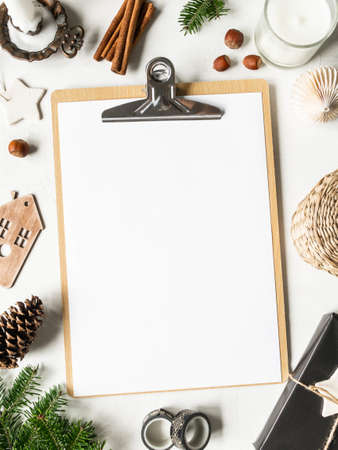 Flat lay of clipboard with blank paper sheet and frame from various Christmas decor on white background. Top view. Copy space Stock fotó