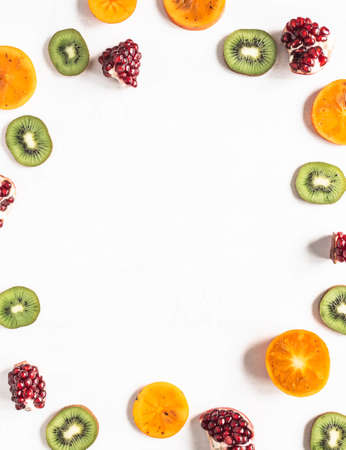 Multicolored seasonal healthy natural fruit frame with persimmon, kiwi, pomegranate slices on white textured background. Copy space. top view. Flat lay