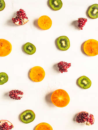 Multicolored seasonal healthy natural fruit background with persimmon, kiwi, pomegranate slices on white background. top view. Flat lay Stock fotó