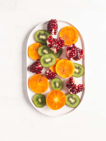 Multicolored seasonal healthy natural fruit - persimmon, kiwi, pomegranate slices on white oval plate. top view. Flat lay. copy space Stock fotó