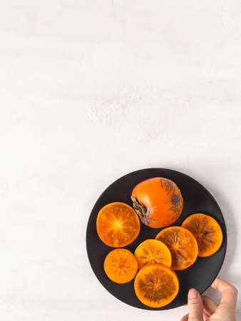 Ripe orange juicy persimmon slices and whole fruit on black plate on white textured background. Top view. copy space. Stock fotó - 159271419