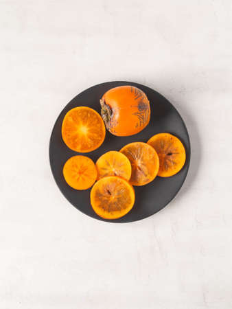 Ripe orange juicy persimmon slices and whole fruit on black plate on white textured background. Top view. copy space.