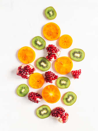 Multicolored seasonal healthy natural fruit composition with persimmon, kiwi, pomegranate slices on white textured background. Copy space. top view. Flat lay Stock fotó