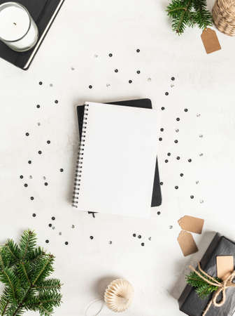 Flat lay of various Christmas decor and notebook with blank page and confetti on white textured background. Top view. Copy space Stock fotó