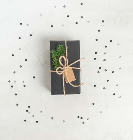 Flat lay wrapped gift black paper with fir tree branch and tag. Christmas reusable sustainable gift wrapping alternative. Z Copy space. Top view.