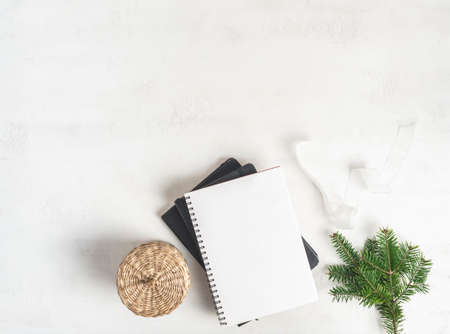 Border of various Christmas decor and notebook with blank page on white textured background. Top view. Copy space Stock fotó
