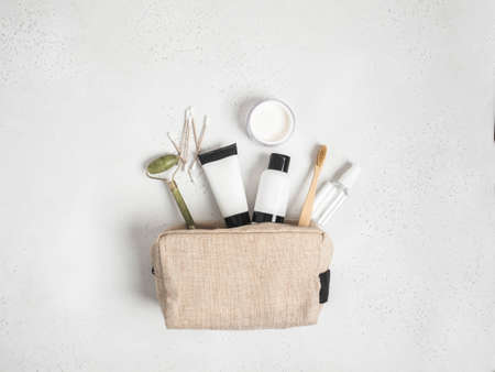 Eco travel cosmetic bag with the necessary means to care for women's skin. Cosmetics, massager with crystals, dry shampoo, cotton buds, toothbrushes in a cosmetic bag on gray background. top view