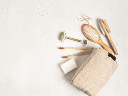 Eco cosmetic bag with a set of items for the care and hygiene of women. Bamboo toothbrush, comb, crystal massager, pumice stone brush, cotton swabs and soap on gray background. Flat lay. copy space. top view. Stock fotó - 159450109
