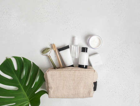 Travel cosmetic bag with the necessary means to care for women's skin. Cosmetics, massager with crystals, dry shampoo, cotton buds, toothbrushes in a cosmetic bag on gray background. top view
