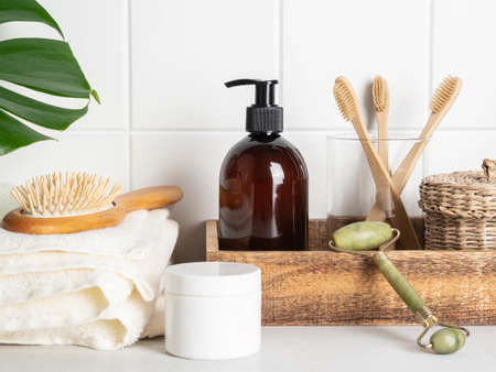 White bath background front view with cosmetic bottle, bath accessories and green leaf on white shelf and wall tiles, Stock fotó