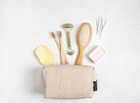 Eco cosmetic bag with a set of items for the care and hygiene of women. Bamboo toothbrush, comb, crystal massager, cotton swabs and soap on gray background. Flat lay. copy space. top view. Stock fotó - 159450070